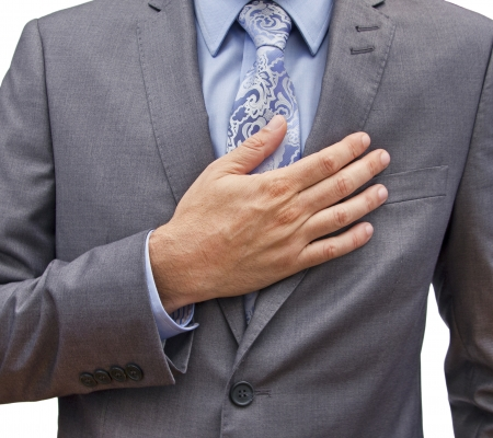 closeup of a man in a suit with his hand over his heart Stockfoto