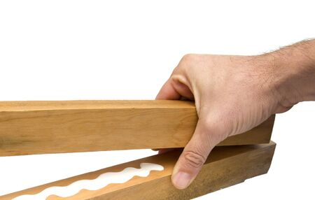 closeup of a hand holding two wood sticks with white glue Stock Photo