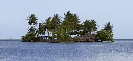 motu: little motu island on pacific ocean with hut bungalow