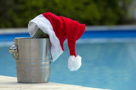 santa claus hoed op een fles wijn bij het zwembad