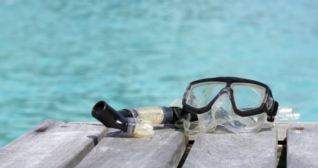 closeup of mask and snorkel on a pier by a blue lagoon photo