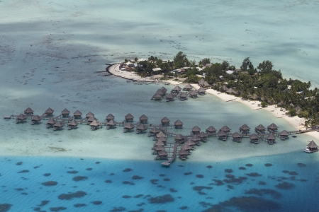 polynesia: aerial view of over water bungalows and the island of bora bora