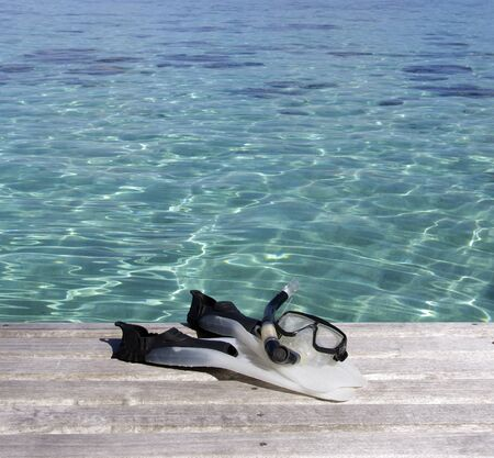snorkeling equipment on a wood pier over a turquoise lagoon