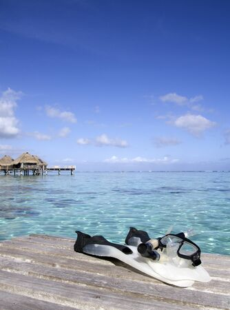 snorkeling equipment on a wood pier over a turquoise lagoon in french polynesia