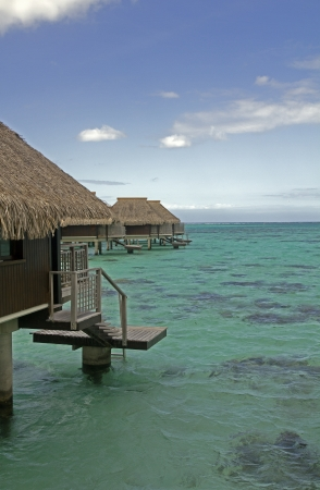 over water bungalow with balcony on a turquoise lagoon Editorial