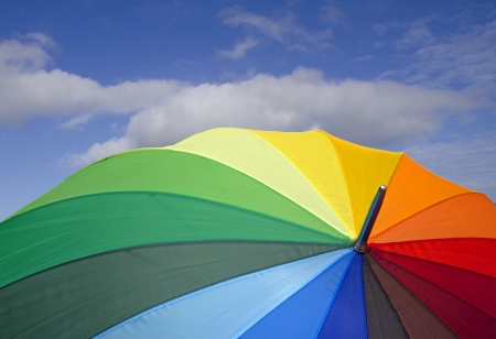 blue green background: closeup of a colorful open umbrella over blue sky