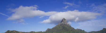 otemanu: top of otemanu mountain in bora bora with blue sky and clouds