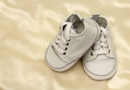 pair of white baby shoe a beige satiny piece