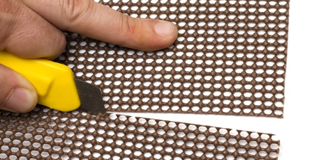 closeup of a hand cutting a plastic sheet with a yellow cutter Stock Photo - 16892595