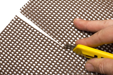 cutter: closeup of a hand cutting a plastic sheet with a yellow cutter