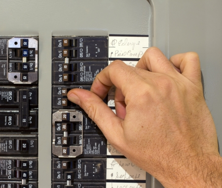 panel: closeup of a hand using an electricity breaker Stock Photo