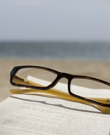 closeup of book and glasses in front of the ocean Stock Photo
