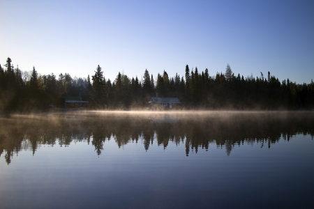 fishing cabin: wild lake with fishing cabin in the morning Stock Photo