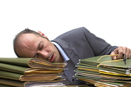 businessman sleeping over a pile of folders