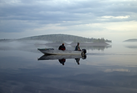 trolling:  two men in a boat fishing on a calm lake
