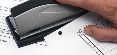 office stapler: hand using a desktop hole punch