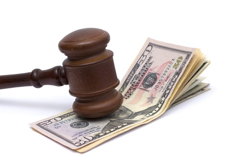 image of a judge mallet and a pile of american money over white