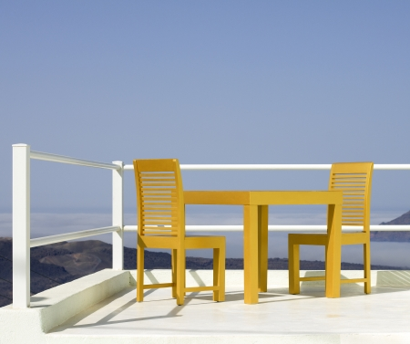 two chairs and a little table facing the sea on a terrace Stock Photo - 22832948