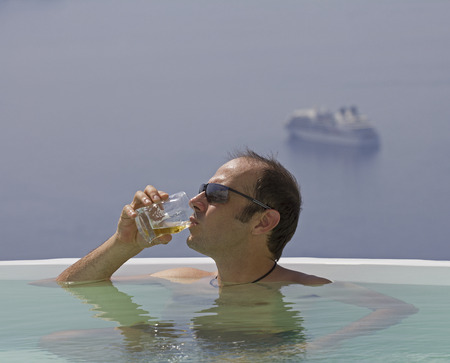 man with a beer in a private pool on a cliff over the sea photo