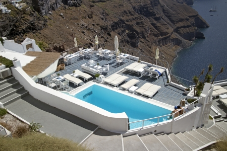 image of a terrace and a swimming pool on  the cliff in santorini greece