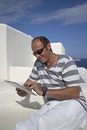 caucasian man using an electronic tablet on the balcony of his hotel in paros greece