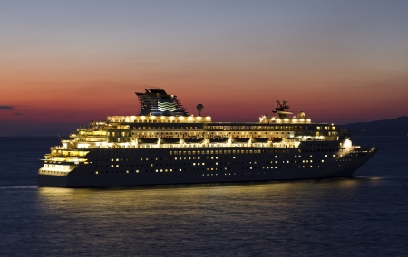 big cruise ship with lights open at sunset photo
