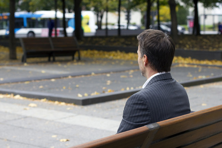 caucasian man sitting on a park bench