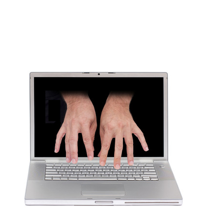 computer control: concept image of a laptop with two hand typing from inside the screen Stock Photo
