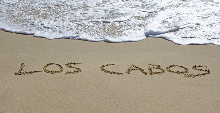 los cabos written on a wet beach sand