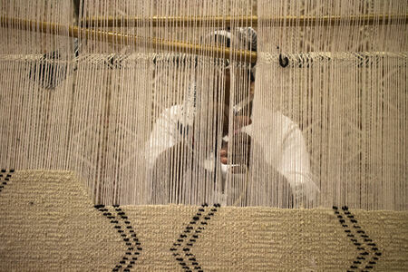african woman making a carpet in a store