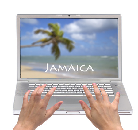 Hands typing on a laptop with Jamaican beach on the screen