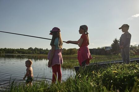 Children fishing on the shore of a large lake. Girls go fishing in the summer in the village. 免版税图像