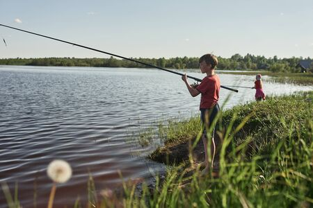 Children fishing on the shore of a large lake. Girls go fishing in the summer in the village.