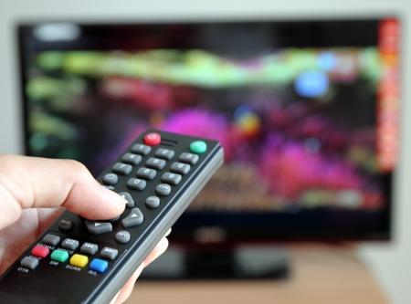 viendo television: Mano que señala un mando a distancia del televisor hacia la televisión