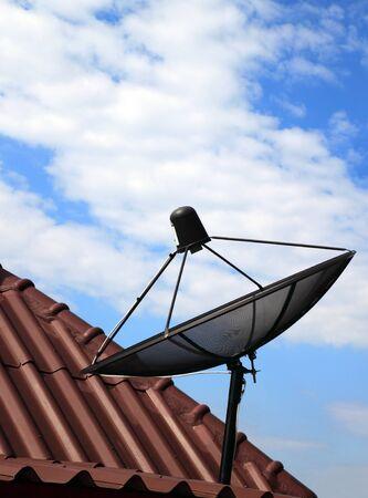 super highway: black satellite dish on  house roof Stock Photo