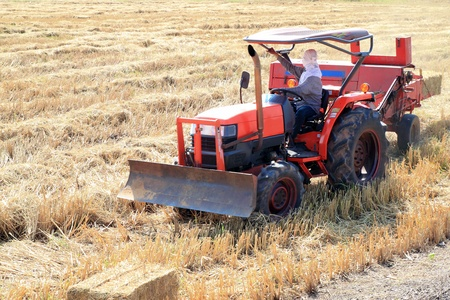 farmer and tractor packing straw in the field at Thailand photo