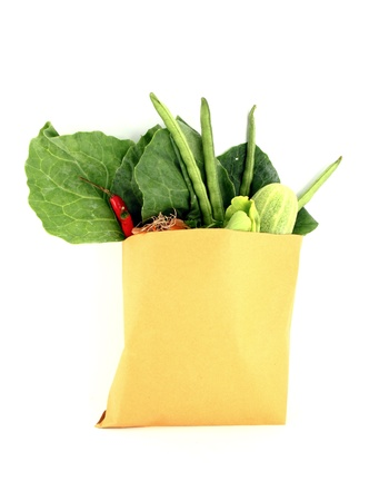 Assorted vegetables in brown bag isolated over white background photo
