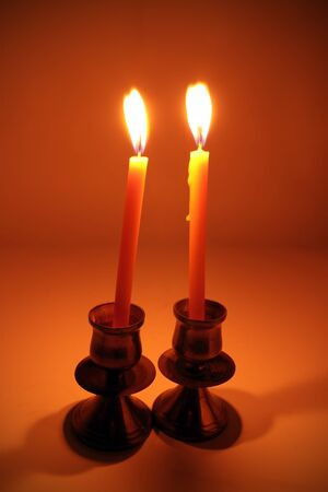 burning candle with antique metal candlestick photo