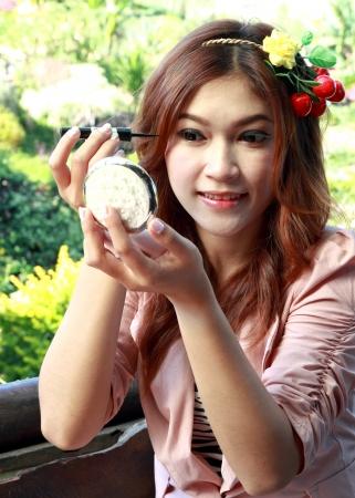 beautiful asian woman applying make up photo