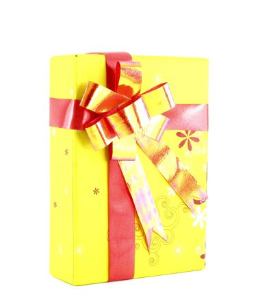 yellow gift box with red ribbon isolated on white background photo