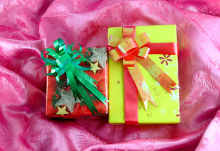 red and yellow gift box with ribbon on pink satin Stock Photo - 11535482