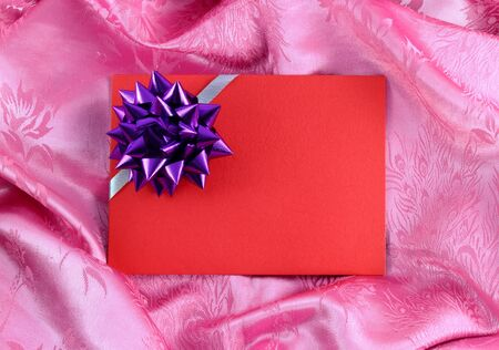 red blank gift card with ribbon on pink satin photo