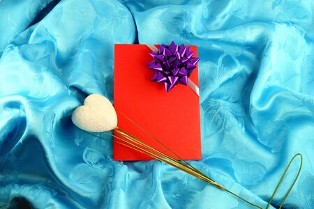 red gift card with ribbon on blue satin photo