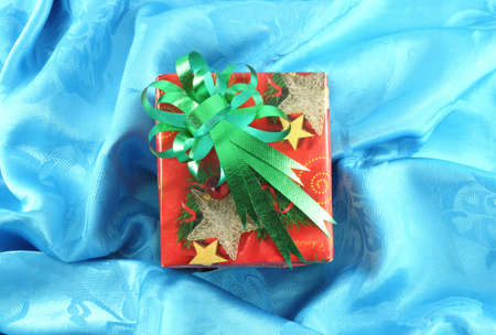 red gift box with green ribbon on blue satin photo