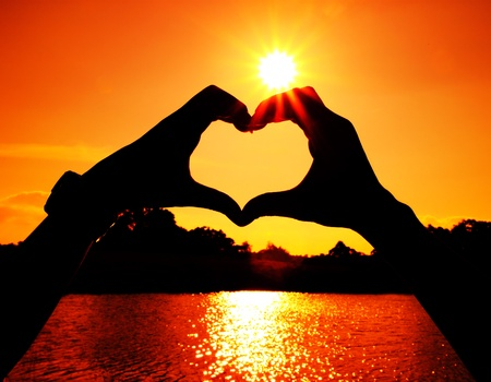 heart shape made with man and woman hands at the sun photo
