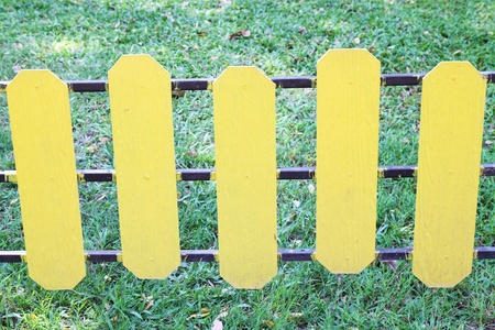 fallow: yellow wooden fence on a green meadow