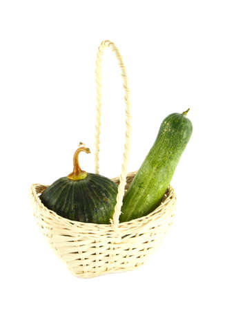 Cucumber and Pumpkin in wicker basket on white photo