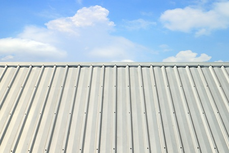 corrugated iron: corrugated aluminum roof with blue sky Stock Photo