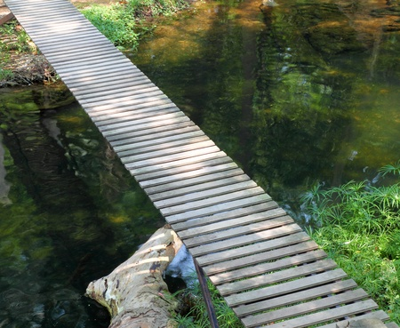 bridge over water: wooden walkway path on stream Stock Photo