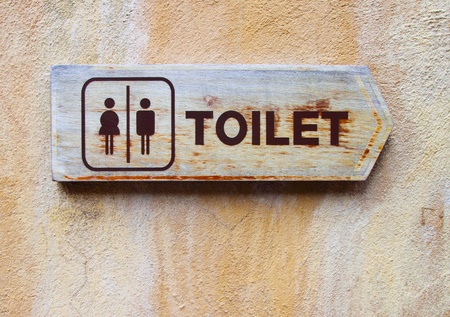 Ancient toilet sign on cement wall photo